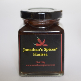 A square shaped glass jar with a black, red and yellow label containing Jonathan's Spices harissa