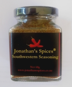 A square shaped glass jar with a black, red and yellow label containing Jonathan's Spices southwestern seasoning