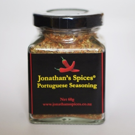 A square shaped glass jar with a black, red and yellow label containing Jonathan's Spices portuguese seasoning